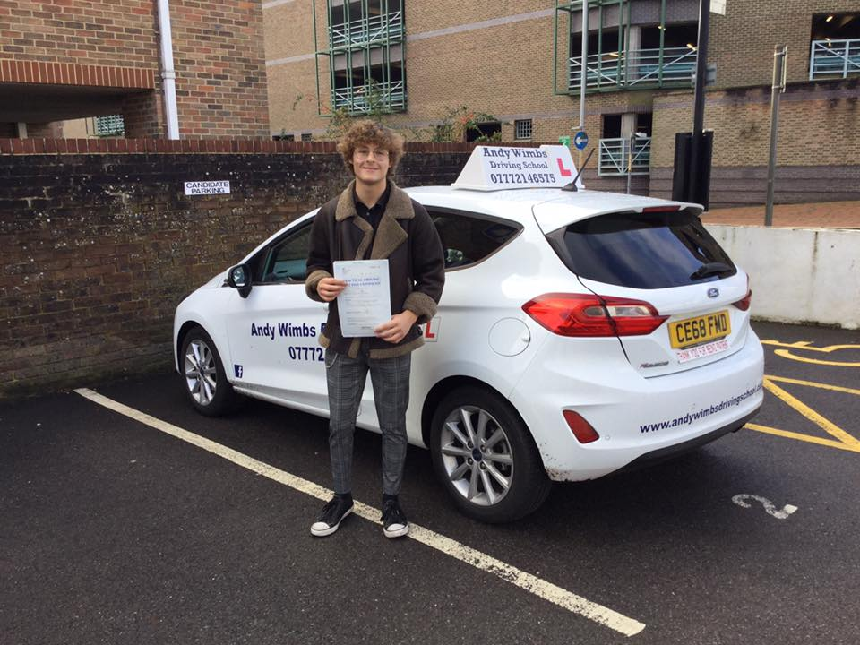 Teen boy holding his pass certificate for driving